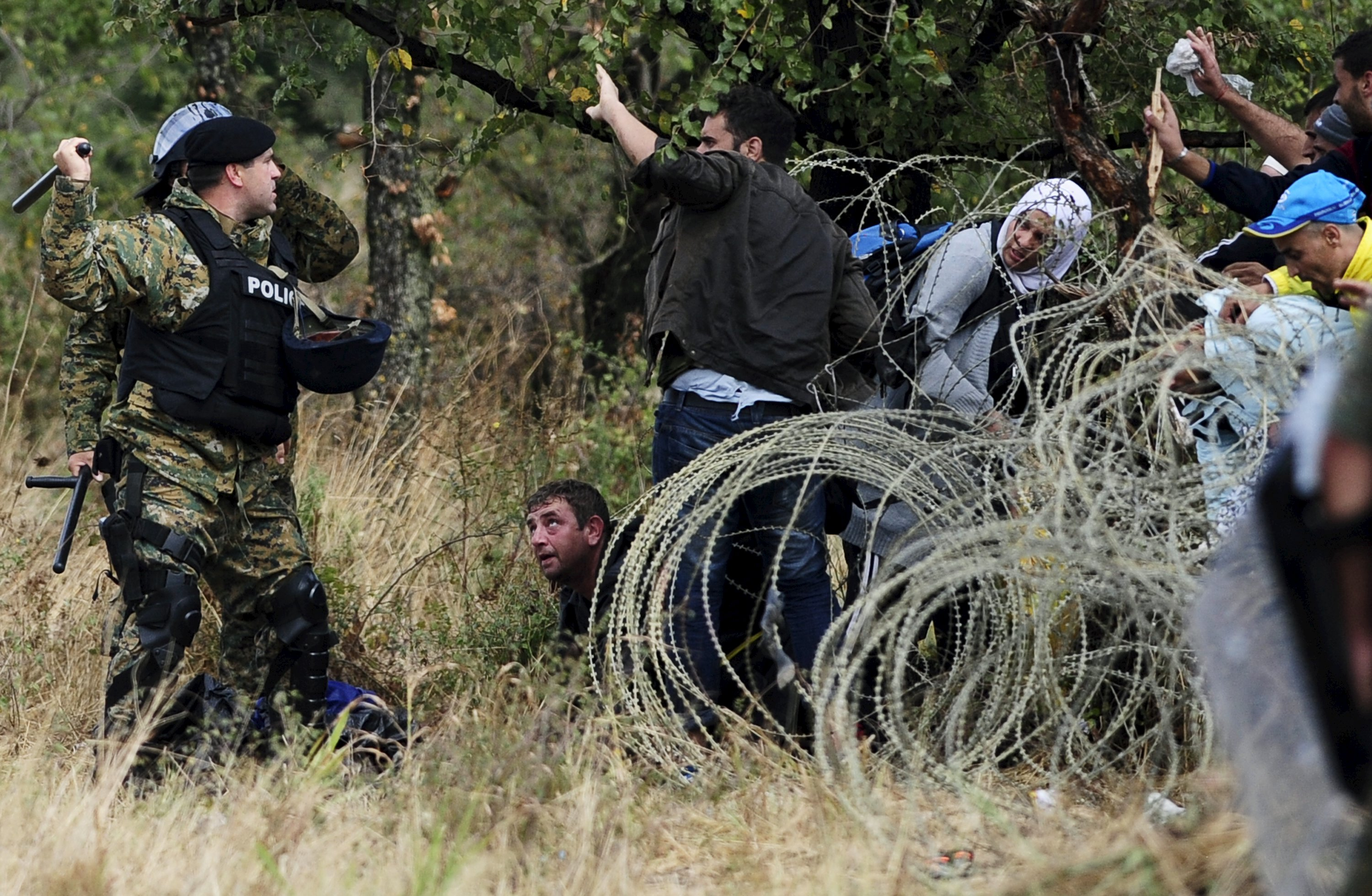 Police stops migrants from crossing Greece's border into Macedonia near Gevgelija, Macedonia, August 22, 2015. Thousands of rain-soaked migrants stormed across Macedonia's border on Saturday as police lobbed stun grenades and beat them with batons, struggling to enforce a decree to stem their flow through the Balkans to western Europe. Security forces managed to contain hundreds in no-man's land. But several thousand others – many of them Syrian refugees - tore through muddy fields to Macedonian territory after days spent in the open without access to shelter, food or water. REUTERS/Ognen Teofilovski
